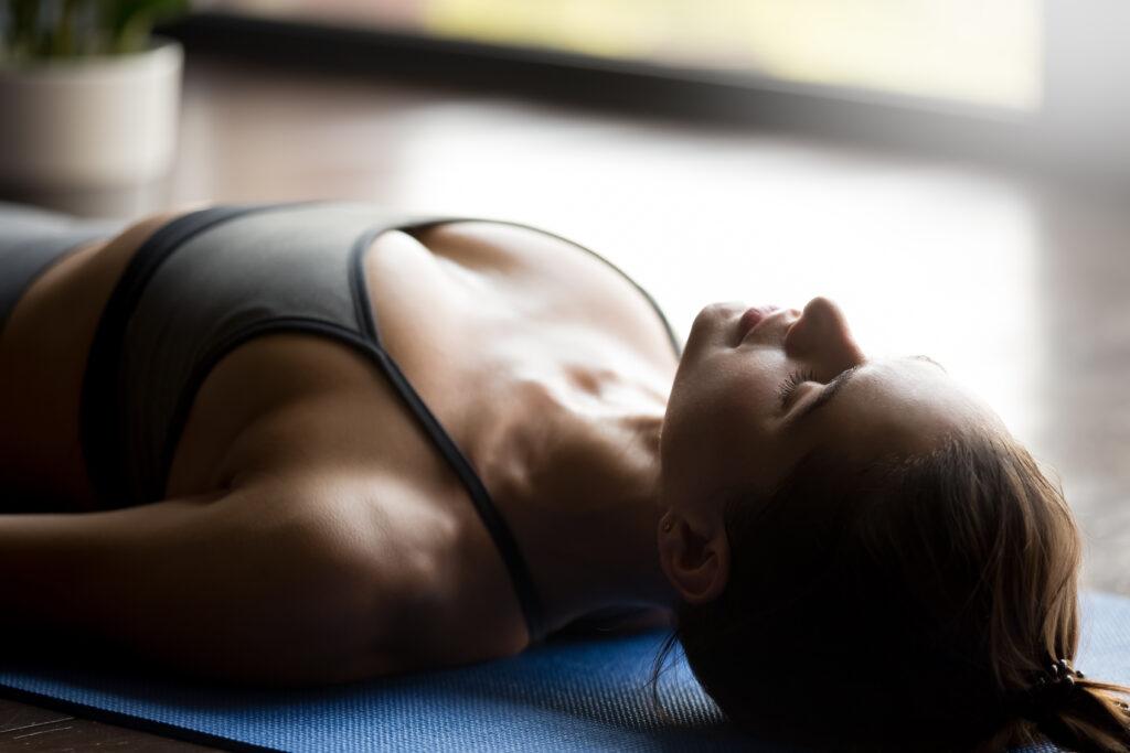 Mujer tumbada realiza ejercicio de relajación y respiración