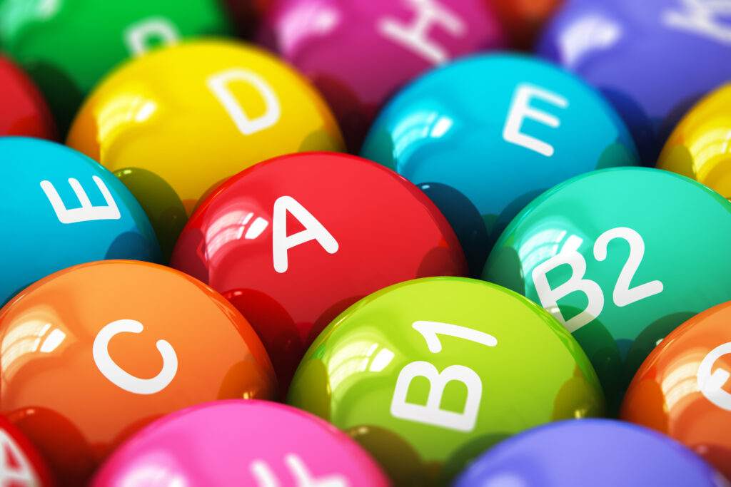 Creative abstract health lifestyle, diet and healthy eating and nutrition food concept: macro view of color balls, pills or tablets with vitamins names with selective focus effect