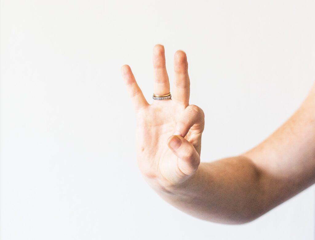 Mano señalando con tres dedos